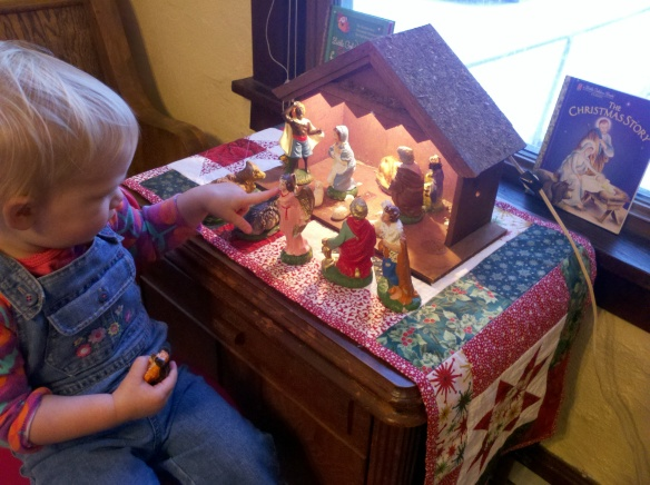 Perched on a step stool, our baby plays with our child-friendly nativity set.