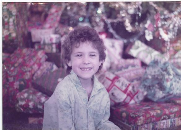 Kathy age six, circa 1984, in front of the behemoth tree on Christmas morning.