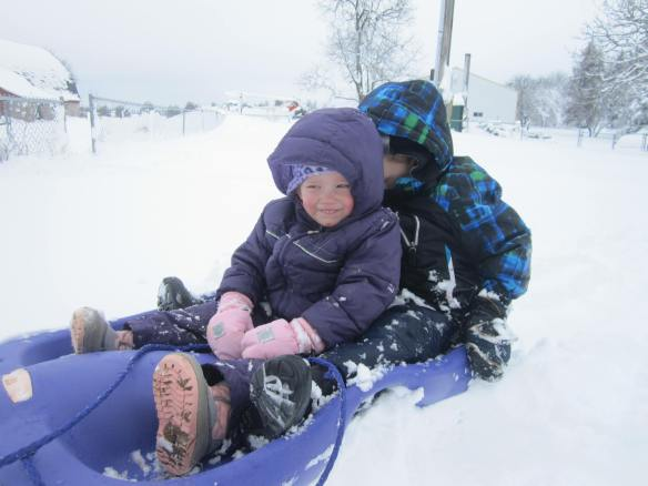 Riding on a sled over knee deep snow.