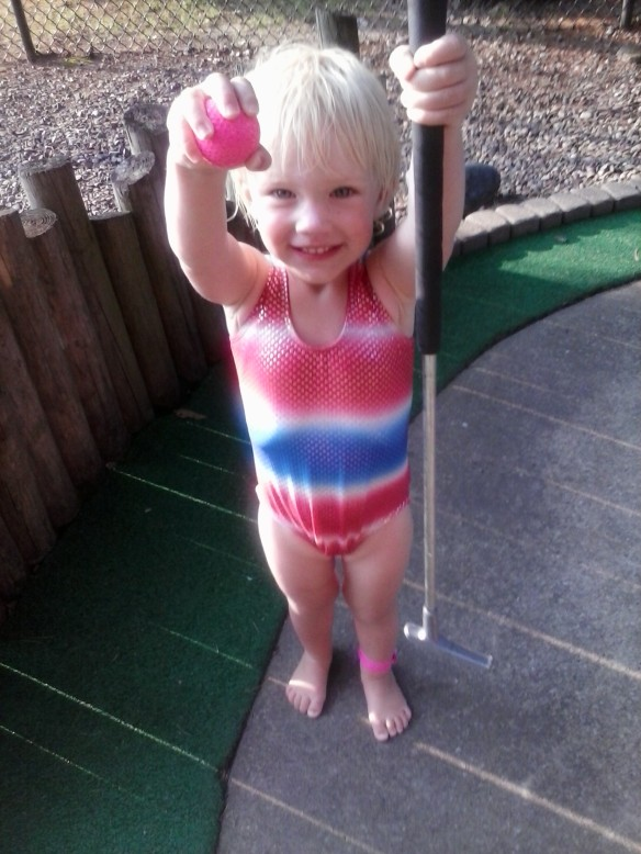 Vacation at its finest: mini golf in a swimming suit with bare feet.