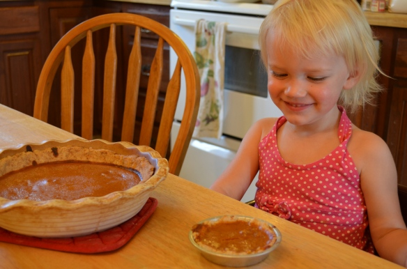 Smiling at her very first little pie.  Seconds later she poked her finger in the big pie and stacked her little pie on top like a pyramid.