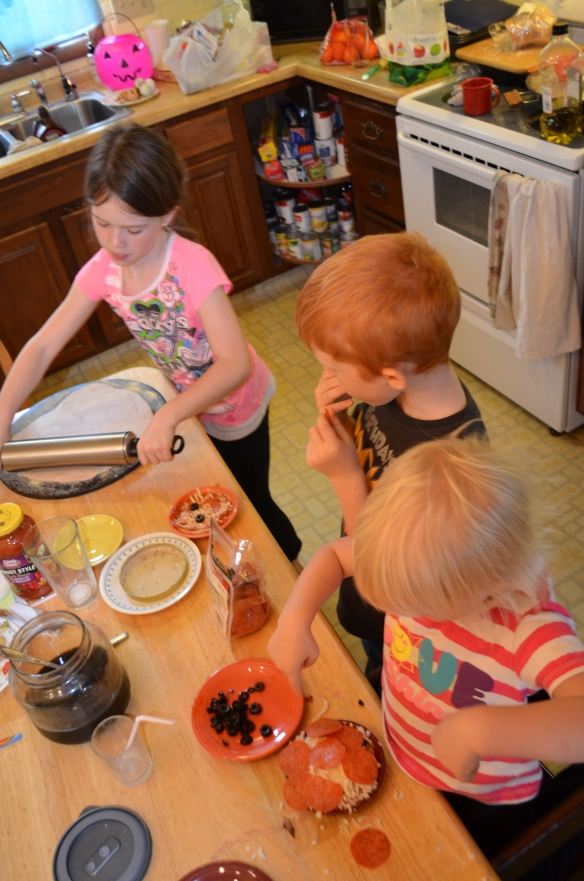 Three kids in a flurry of gobbling olives and making pizza creations.