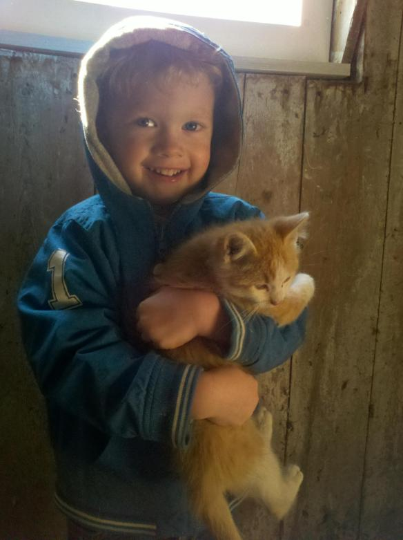 Mighty happy to hold a fluffy kitten after watering chickens.